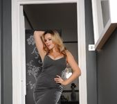 Jodie Gasson teasing in her long grey dress in the doorway 2