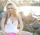 Lily poses and shows her pink panties on the rocks 13