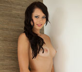 Natasha Belle strips naked while posing against the wall 8