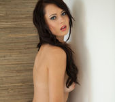 Natasha Belle strips naked while posing against the wall 15
