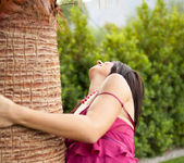 Natasha Belle strips out of her dress next to a palm tree 2