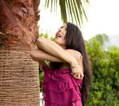 Natasha Belle strips out of her dress next to a palm tree 13