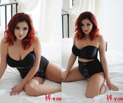 Lucy V teasing on the bed in her black bras and high waist