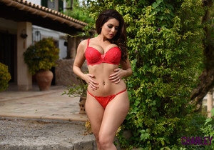 Charley teasing outdoors on the steps in red lingerie